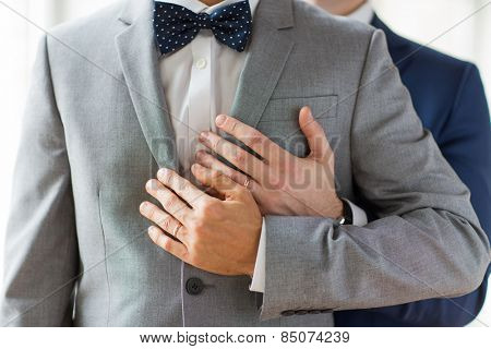 people, celebration, homosexuality, same-sex marriage and love concept - close up of happy male gay couple with wedding rings hugging