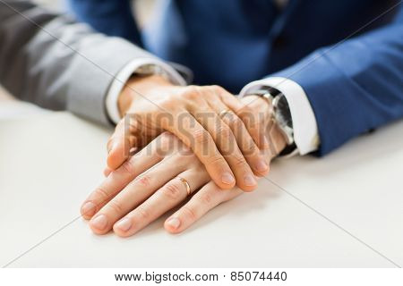 people, homosexuality, same-sex marriage and love concept - close up of happy male gay couple hands with wedding rings on