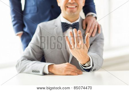 people, celebration, homosexuality, same-sex marriage and love concept - close up of male gay couple with wedding rings on putting hand on shoulder