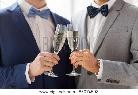 people, celebration, homosexuality, same-sex marriage and love concept - close up of happy married male gay couple in suits and bow-ties drinking sparkling wine and clinking glasses on wedding