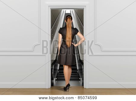 Girl standing back to doorway going on escalator