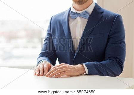 people, fashion, style and wedding concept - close up of best man or groom in suit and bow-tie at table