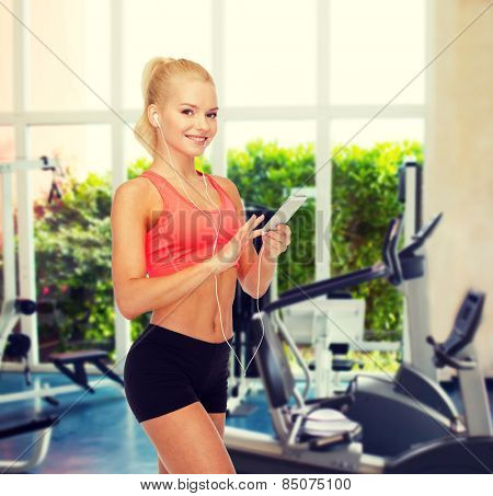 sport, fitness, technology, internet and healthcare - smiling sporty woman with smartphone and earphones