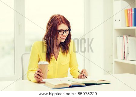 education concept - smiling student girl in eyeglasses reading books ana taking notes in library