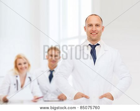 healthcare, profession, teamwork and medicine concept - smiling male doctor in white coat over group of medics