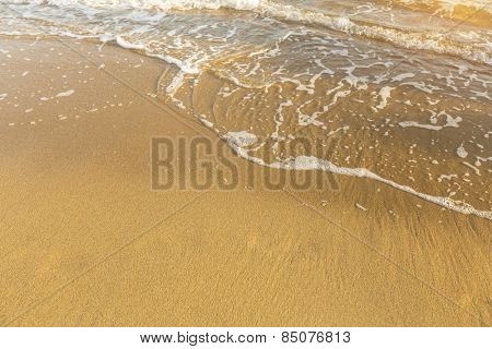 Soft wave on the beach and texture golden sea of sand.