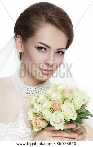 Young beautiful bride with stylish make-up and hairdo holding bouquet over white background