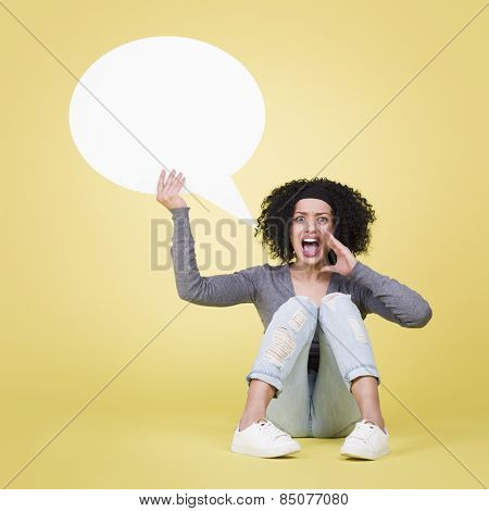 Shouting woman being mad holding a empty white sign board with copy space, isolated on yellow background.