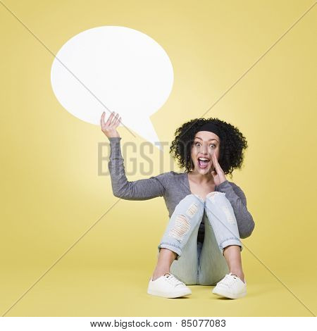 Happy woman being excited holding a white blank sign board with empty copy space, isolated on yellow background.