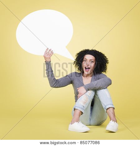 Excited woman holding a blank sign board with empty copy space, isolated on yellow background.