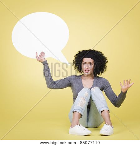 Wondering woman being irritated holding a blank white paper speech bubble with empty copy space, isolated on yellow background.