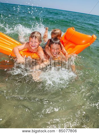 Three kids having fun floating on a inflatable mattress in the sea