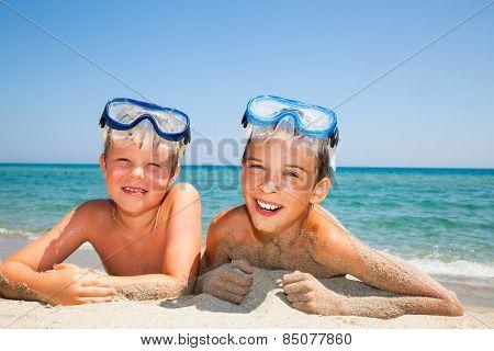 Happy boys wearing snorkeling gear relaxing on the beach