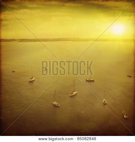 Seascape with fishing boats at sunset in grunge and retro style.