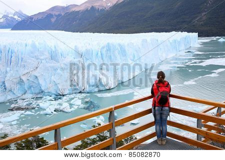 Tourist standing on footbridge in front of Perito Moreno Glacier