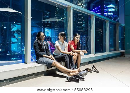 Overworked business people after hour resting in front of nightly city skyline