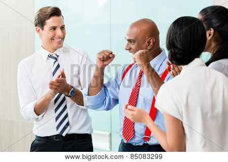Business team celebrating success applauding and shaking fists