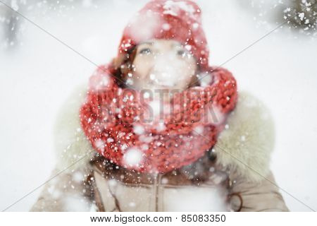 young woman with red scarf playing with snow, selective focus on the snowflakes