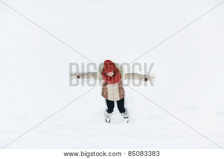 woman laying on the ground after a fresh snow fall
