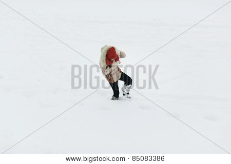 young woman walking on the deep snow