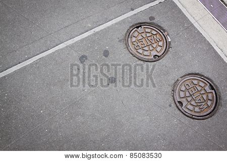 Two round cast iron manhole cover plates with the word Water on them over the openings on a sidewalk to water supply.