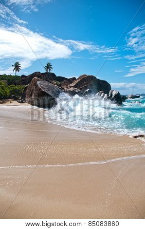 Water Splash at the Attractive Beach of Virgin Gorda Island with Big Rocks, Plants and Trees on a Tropical Climate.