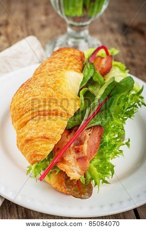 Fresh croissant for breakfast stuffed with bacon, lettuce, chard and avocado