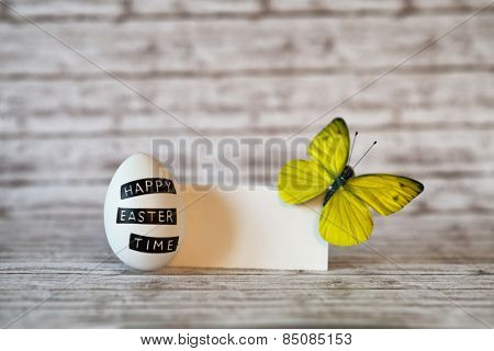 Close up White Easter Egg with Yellow Green Butterfly on Upper Right Corner of a Blank Greeting Card on Top of a Wooden Table with Fuzzy Background.