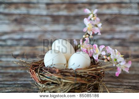 Close up Three White Chicken Eggs in a Nest, with Small Lovely Flowers on a Stem, Placed on Top of the Table with Fuzzy Background.
