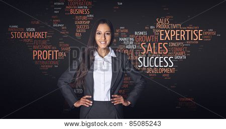 Confident Happy Businesswoman with Both hands on the Waist Standing in Front of a World Map in a Word Cloud Design with Business Tags.