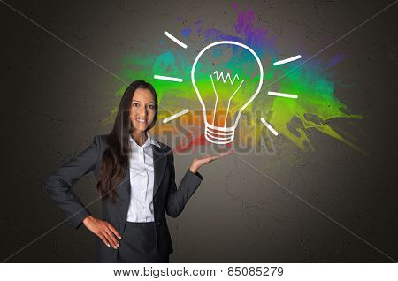 Young Confident Businesswoman on Gray Gradient Showing Abstract Glowing Bulb Drawing with an Abstract Colorful Background.