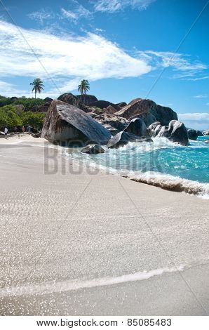 Attractive Beach with Turquoise Sea Water, Granite Boulders and Trees Under Blue and White Sky on a Tropical Climate. Located at the Virgin Gorda Island in the Caribbean