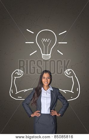 Confident Young Office Woman Smiling In Front of Gray Gradient Background with Conceptual Arm Muscles and Glowing Bulb Drawing.