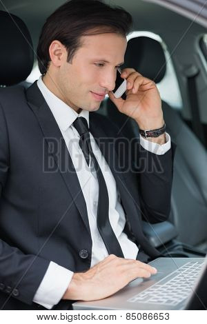 Businessman working in the drivers seat in his car