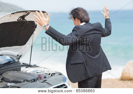 Anger businessman looking at engine of his car