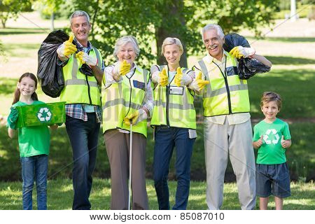 Happy family collecting rubbish with thumbs up on a sunny day