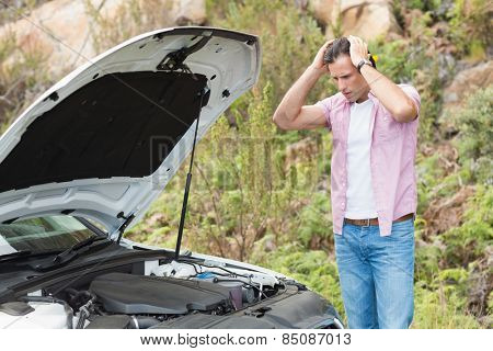 Stressed man looking at engine of his car