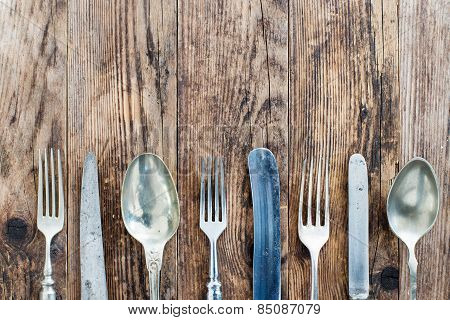 Spoon Knife And Fork On The Wooden Board.