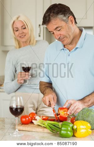 Mature couple having red wine while making dinner at home in the kitchen