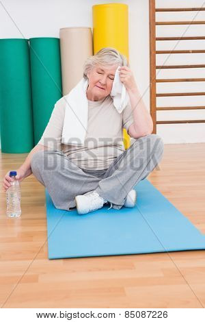 Tired senior woman on exercise mat in fitness mat