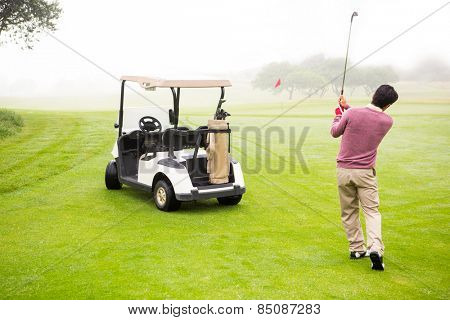 Golfer teeing off next to his golf buggy at the golf course