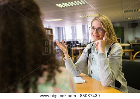 Student getting help from tutor in library at the university