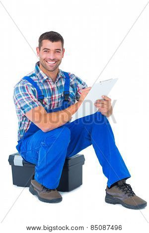 Full length portrait of happy handyman writing on clipboard while sitting on toolbox over white background