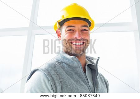 Portrait of smiling manual worker wearing hardhat in building