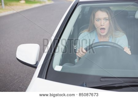 Surprised young woman in her car