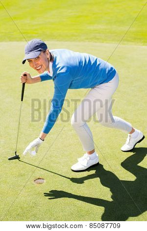 Female golfer picking up golf ball on a sunny day at the golf course