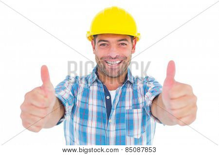 Portrait of smiling manual worker gesturing thumbs up on white background