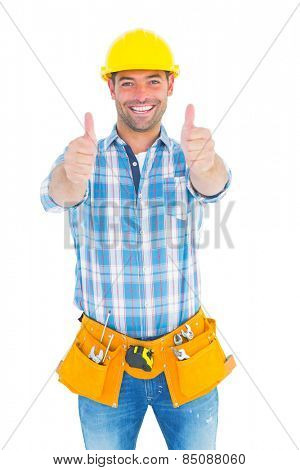 Portrait of happy repairman wearing tool belt while gesturing thumbs on white background