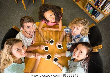 High angle portrait of college students holding coffee mugs on table