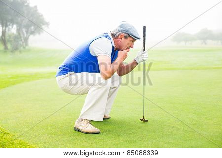 Serious golfer kneeling on the putting green on a foggy day at the golf course